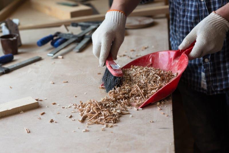 Плотник в мастерской плотничества подметает опилк, стоковые фотографии rf
