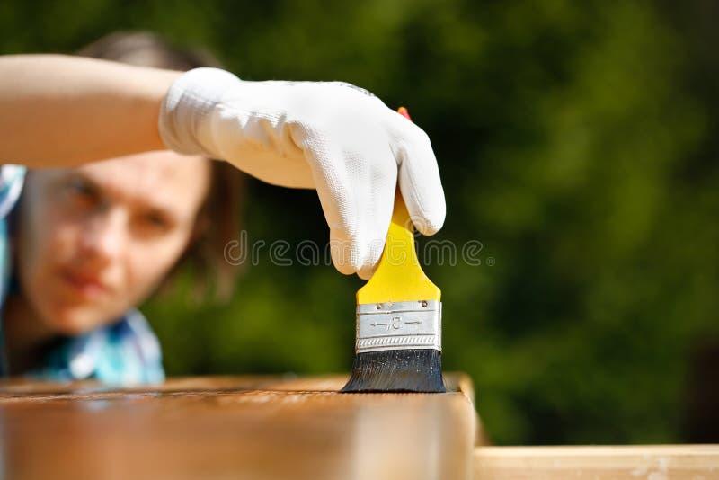 Плотник женщины проверяя свеже покрашенную древесину стоковые изображения