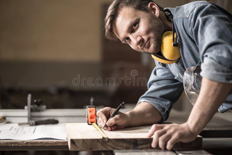 Плотник измеряя деревянную доску стоковые фотографии rf