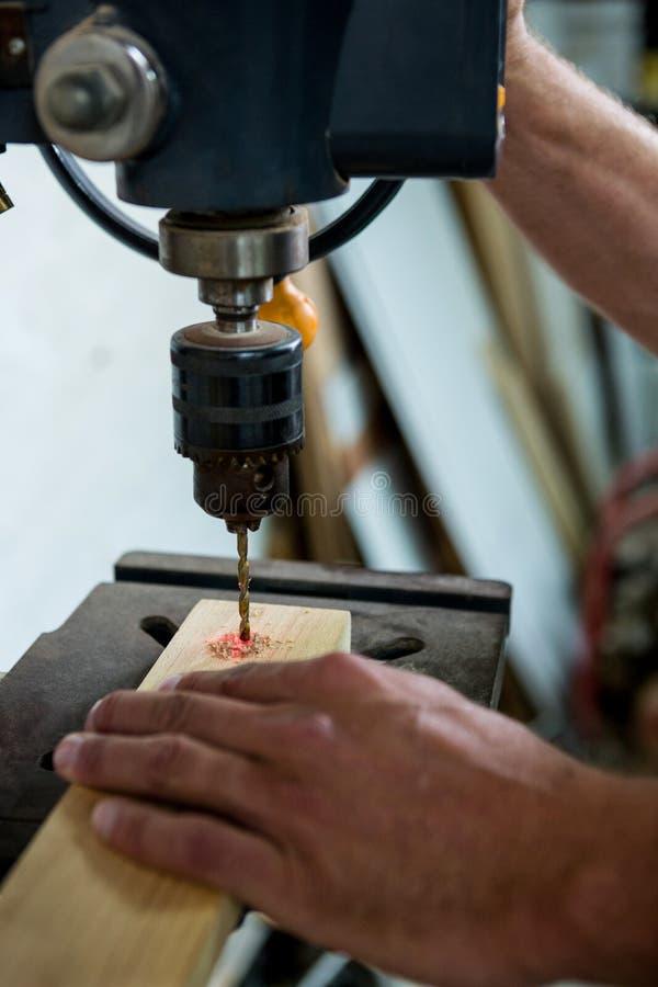Плотник используя сверло стоковые фото