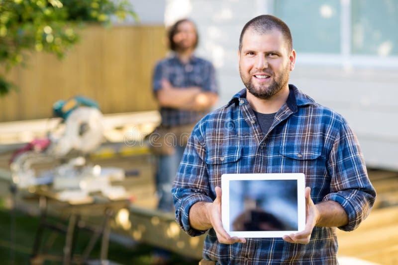 Плотник показывая таблетку цифров с сотрудником стоковые изображения