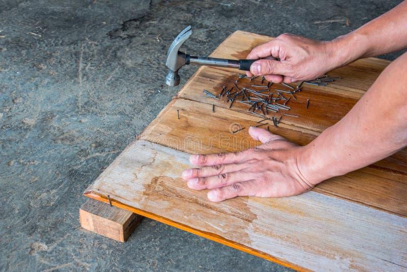 Плотник пригвождая деревянную доску для того чтобы сделать мебель стоковое изображение rf