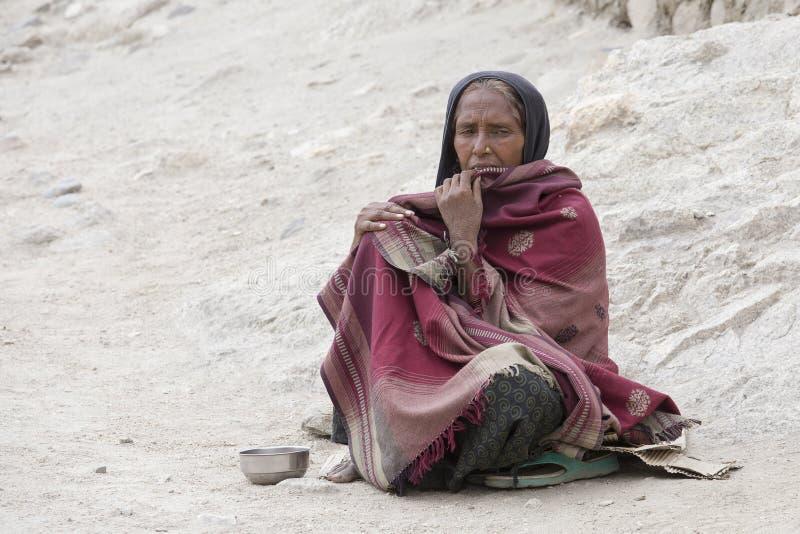 Плохая женщина умоляет для денег от прохожего на улице в Leh, Ladakh Индия стоковая фотография