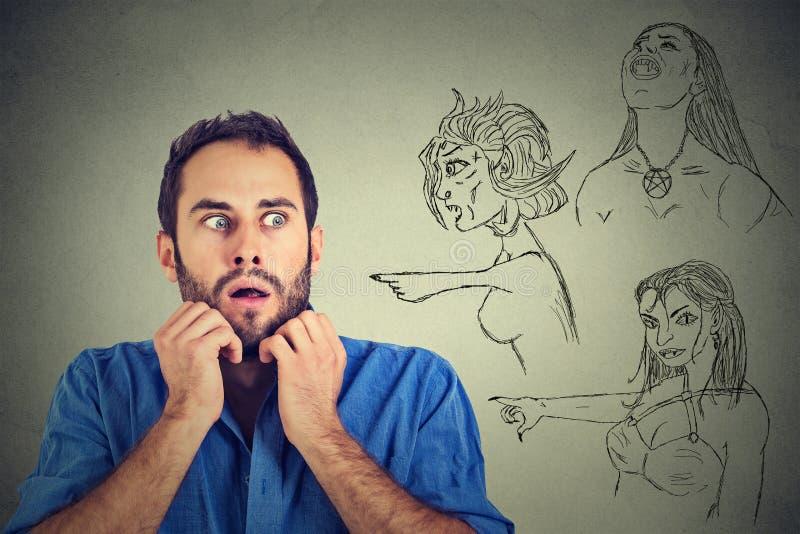 Плохие злие женщины указывая на усиленный тревоженый молодой человек стоковые фотографии rf