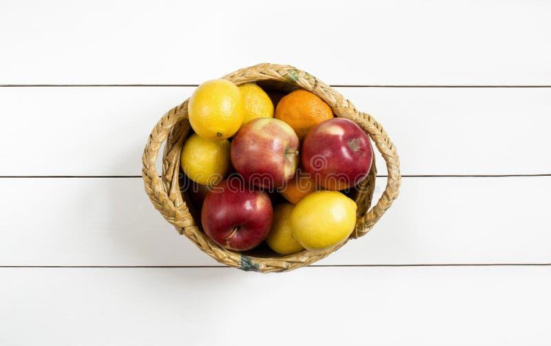 Плодоовощи в плетеной корзине на белом деревянном столе стоковое изображение rf