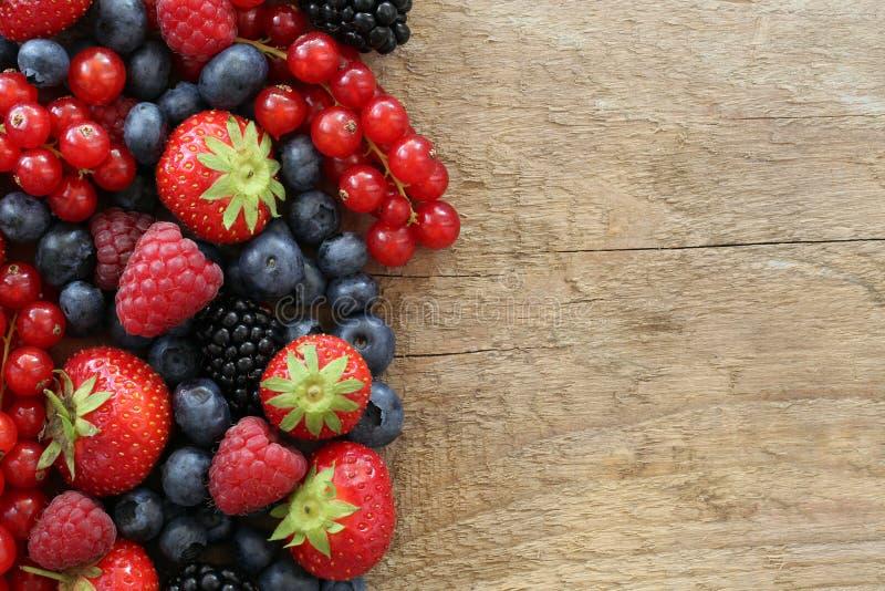 Плодоовощи ягоды на деревянной доске стоковые изображения