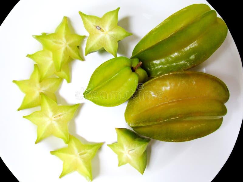 Плодоовощ яблока карамболы или звезды, кусок плодоовощ карамболы или плодоовощ яблока звезды на белом блюде стоковые изображения