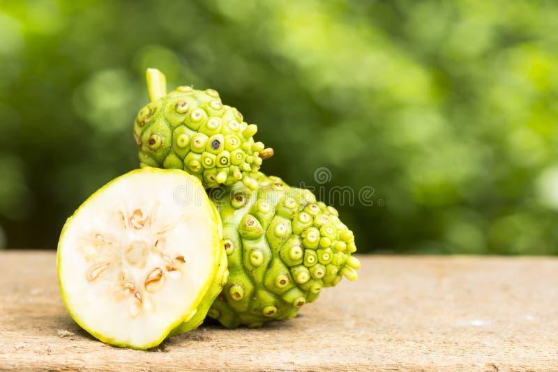 Плодоовощ Noni и кусок noni на предпосылке деревянного стола и зеленого цвета Плодоовощ для здоровья и трава для здоровья 110 стоковое изображение rf