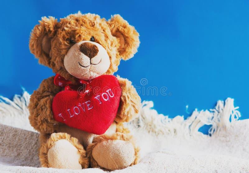 Плюшевый медвежонок и большое красное сердце при изолированный текст я тебя люблю стоковые изображения