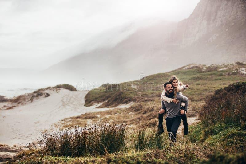 пляж давая женщину зимы piggyback человека стоковое изображение
