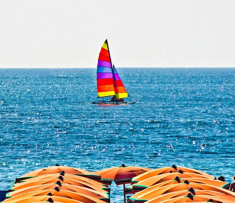 Пляж лета с зонтиками и шлюпкой на заднем плане стоковое фото