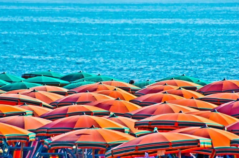 Пляж лета с оранжевыми зонтиками стоковое изображение rf