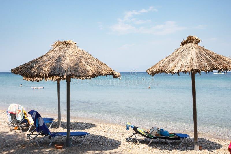 Пляж с зонтиками солнца соломы и sunbeds стоковое фото