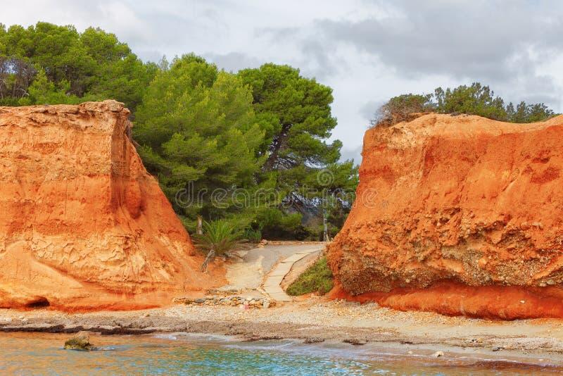 Пляж Caleta в Ibiza, со своей красной землей, Испания стоковые фото
