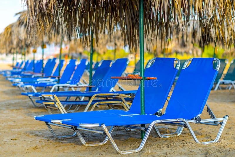 Пляж Sunbeds с зонтиками соломы стоковая фотография