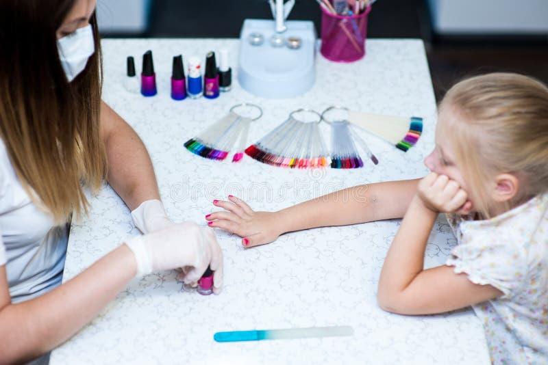 Работайте в мастере студии ногтя с ребенком клиента стоковые фотографии rf
