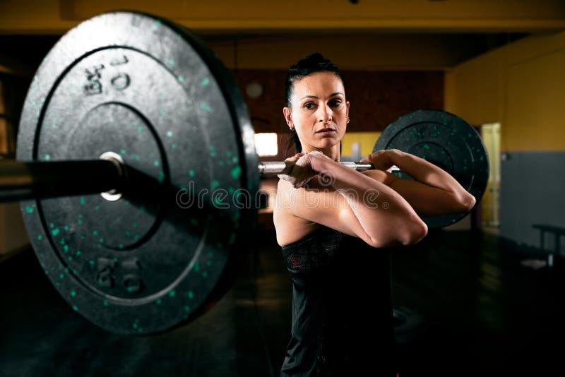 Работайте с тяжеловесом, мышечной девушкой удерживание весит стоковая фотография rf