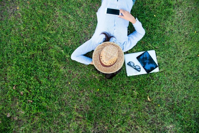 Работать используя таблетку компьтер-книжки умную и умный телефон кладет вниз на электронную таблицу чтения поля зеленой травы стоковое изображение