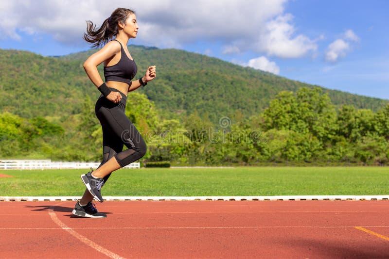 Работать красивой молодой азиатской женщины бежать в утре на идущем следе стоковые фотографии rf