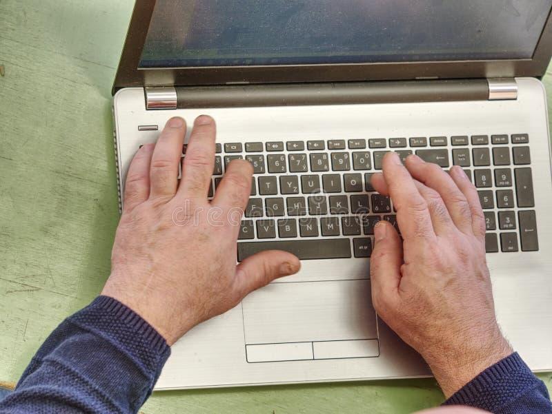 Работать на конце ноутбука вверх рук старика стоковое фото