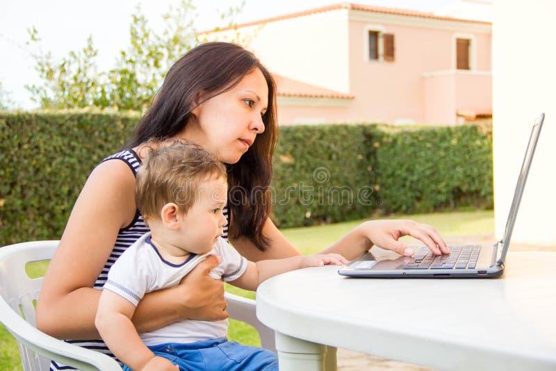 Работать совместно так коммерсантка потехи жизнерадостная молодая красивая смотря ее ребёнок с улыбкой пока сидящ на ее работе стоковое фото rf
