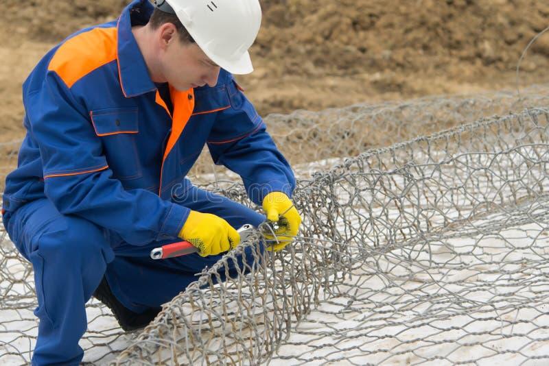 Работающ в голубой форме, свяжите сетку для клеток под камнями для того чтобы улучшить берег, конец-вверх стоковые фотографии rf