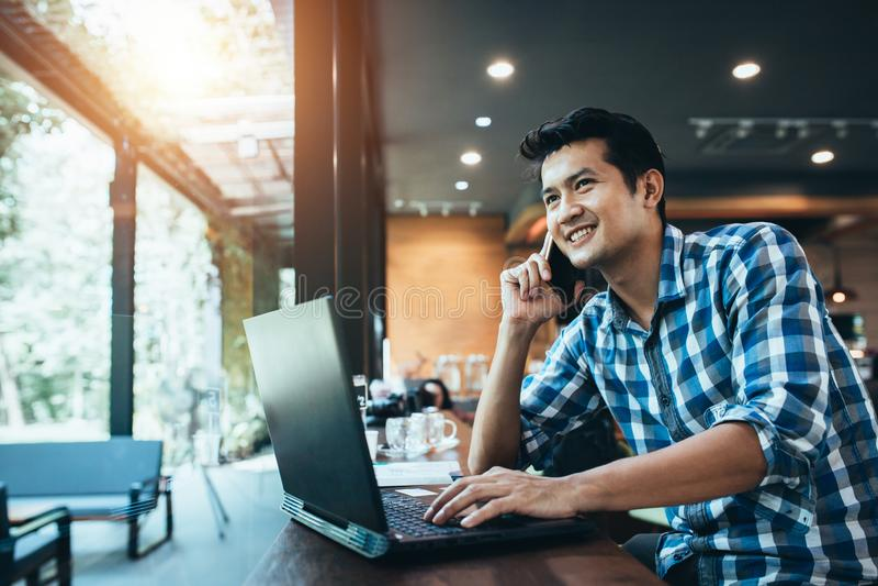 Работа азиатского человека независимая на сенсорной панели компьютера пока говорящ по умному телефону со счастливой улыбкой, ноут стоковое изображение rf