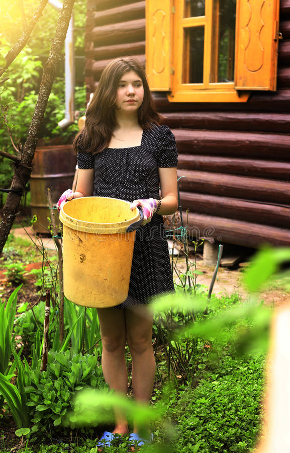 Работа девушки подростка в саде с желтым пластичным ящиком стоковое фото rf
