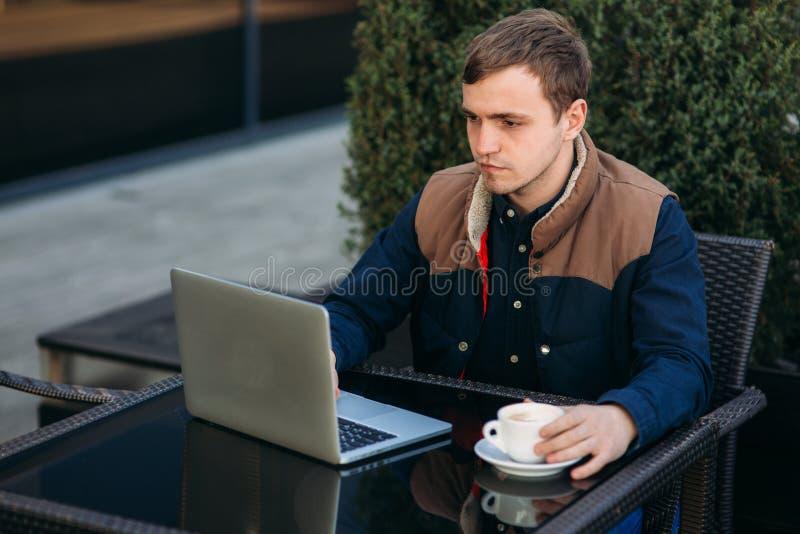 Работа маклера на его ноутбуке в кафе Человек использовать его мозг для того чтобы заработать деньги стоковые фотографии rf