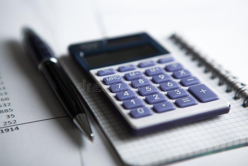 Работа на калькуляторе и бумагах стоковая фотография