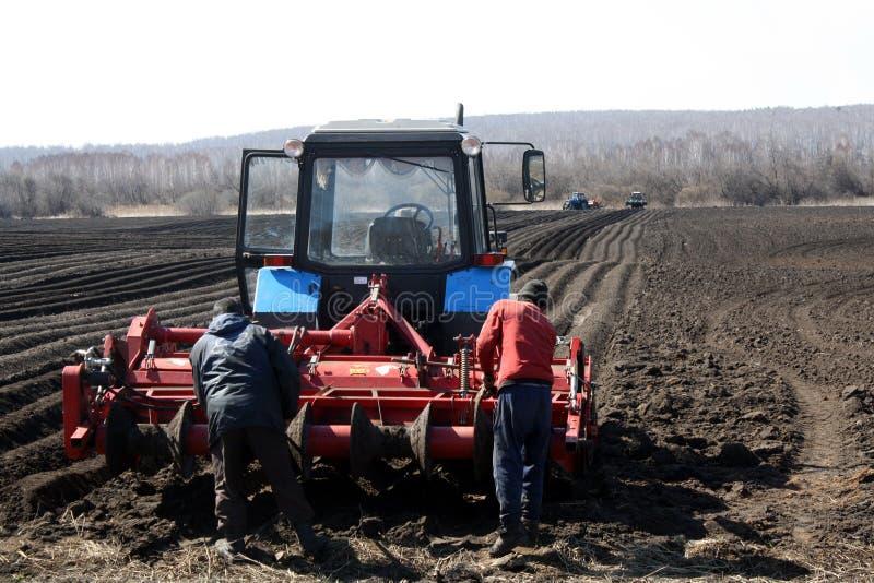 Работа на местах МОСКВЫ - 2-ОЕ МАЯ 2019 на подготовке земли весной для засевать Черная земля двигает прочь в перспективу стоковые фотографии rf