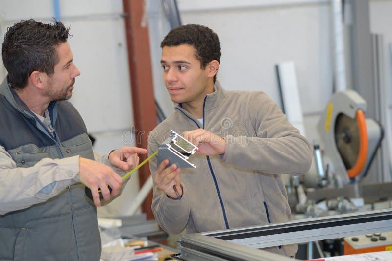 Работа работника взрослого менеджера одобрительно на фабрике окон PVC стоковое изображение rf