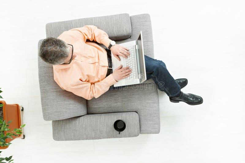 работа человека компьтер-книжки кресла сидя стоковое фото