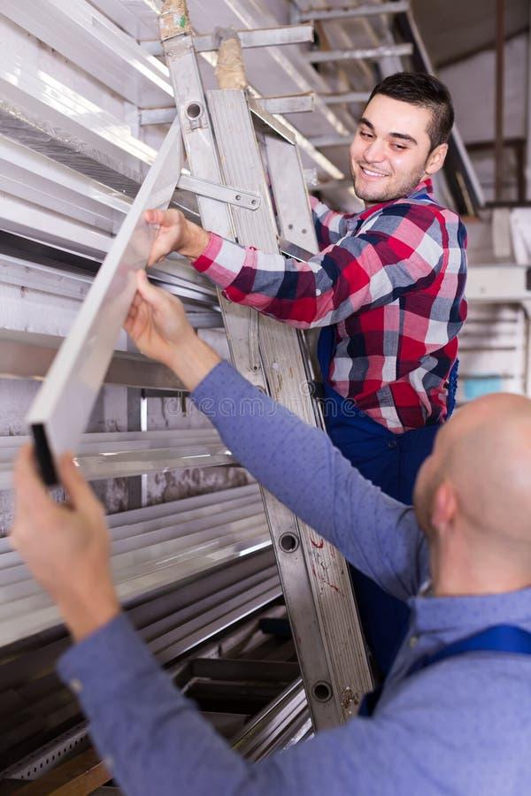 2 работника выбирая профиль окна PVC стоковые изображения