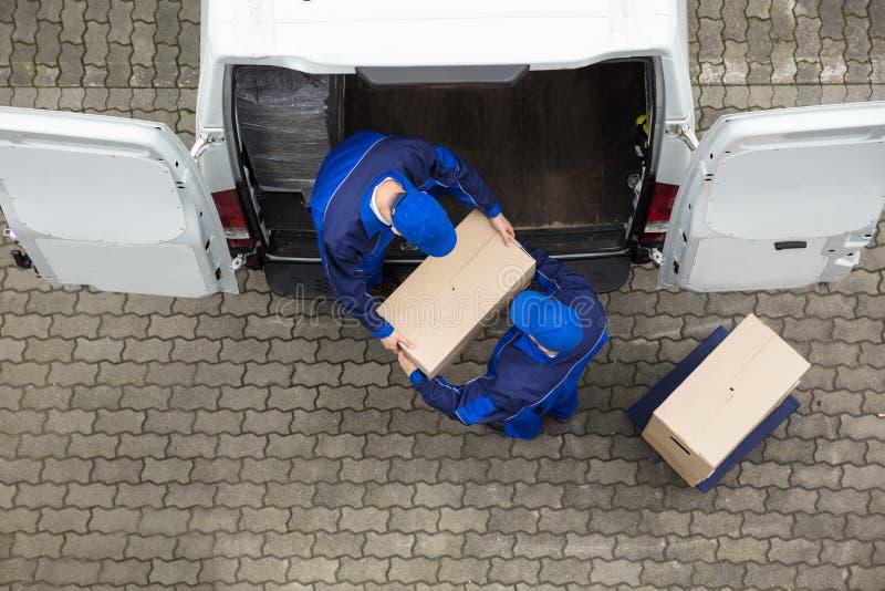 2 работника доставляющего покупки на дом разгржая картонную коробку от тележки стоковое изображение rf