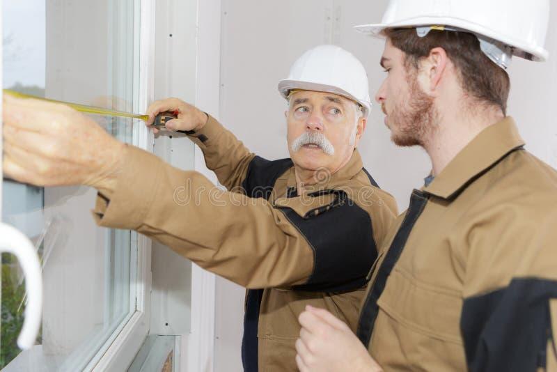 2 работника измеряя окна стоковые фотографии rf