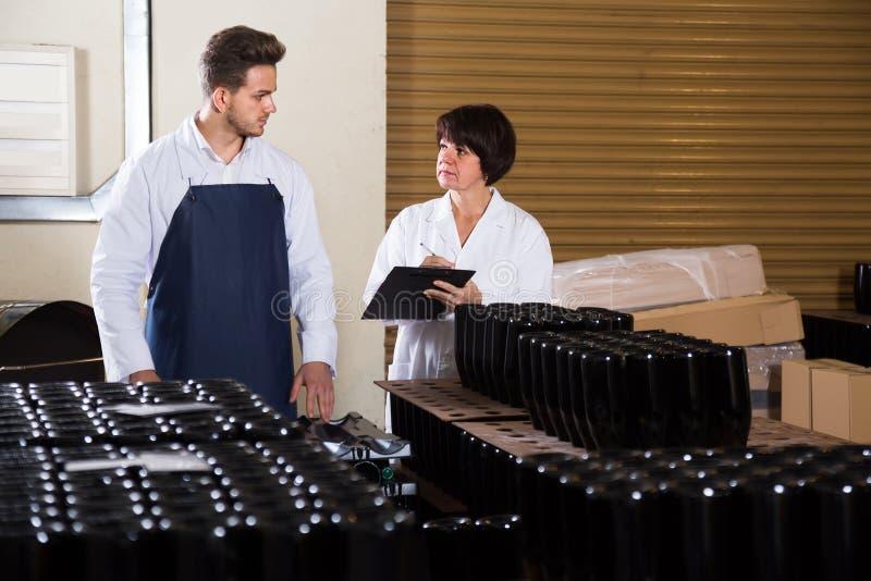 2 работника контролируя количество бутылок вина на игристом вине стоковое фото rf