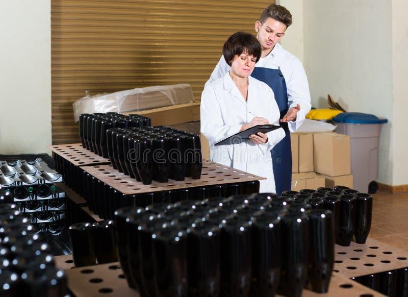 2 работника контролируя количество бутылок вина на игристом вине стоковое изображение