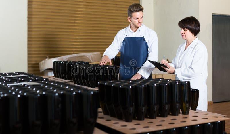 2 работника контролируя количество бутылок вина на игристом вине стоковая фотография rf