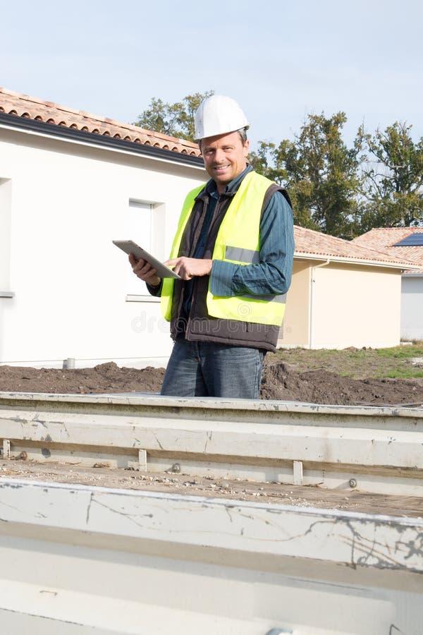работника мастера человека планшет здания привлекательного наблюдая outdoors нося шлем конструкции стоковое изображение rf