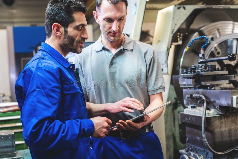 2 работника обсуждая проект перед машиной токарного станка CNC стоковое изображение