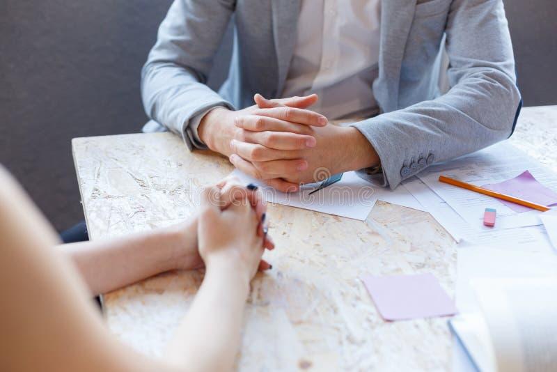 2 работника офиса сидят на столе, складывая их руки в сметанообразном замке стоковая фотография