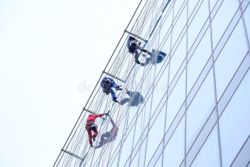 3 работника очищая обслуживание окон на высоком здании подъема стоковые изображения