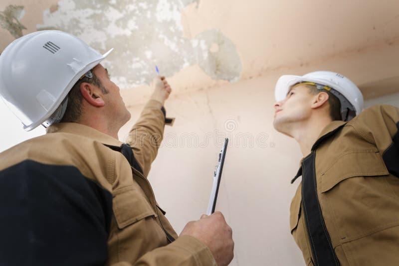 2 работника проверяя потолок здания стоковая фотография rf