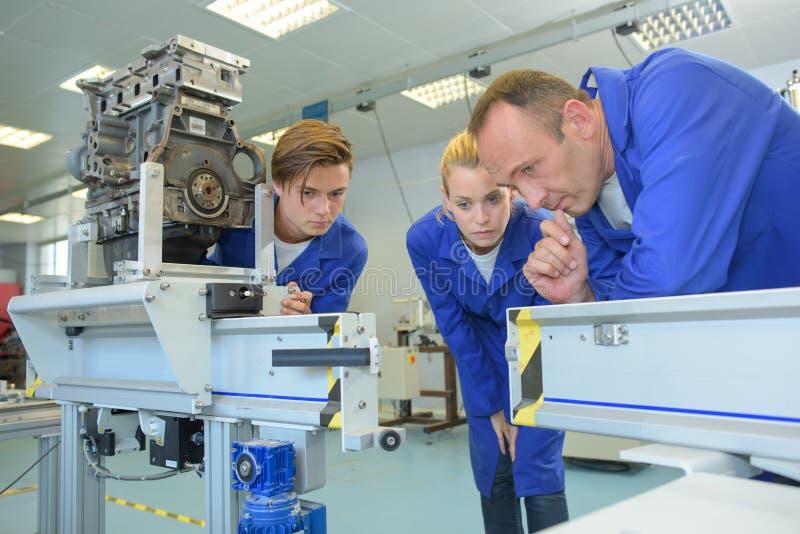 3 работника смотря машинное оборудование созерцательно стоковая фотография rf