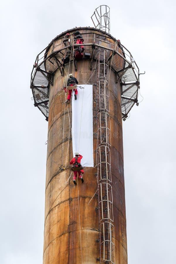 Работники взбираясь на большой печной трубе стоковое изображение rf