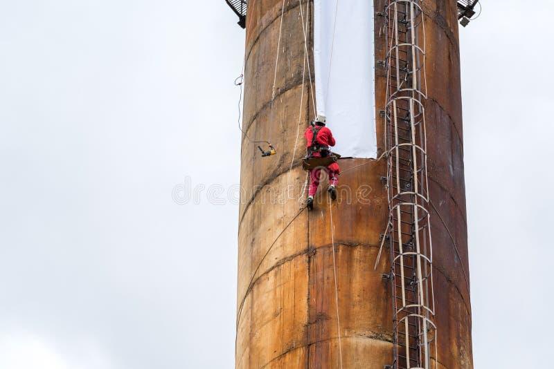 Работники взбираясь на большой печной трубе стоковое фото rf