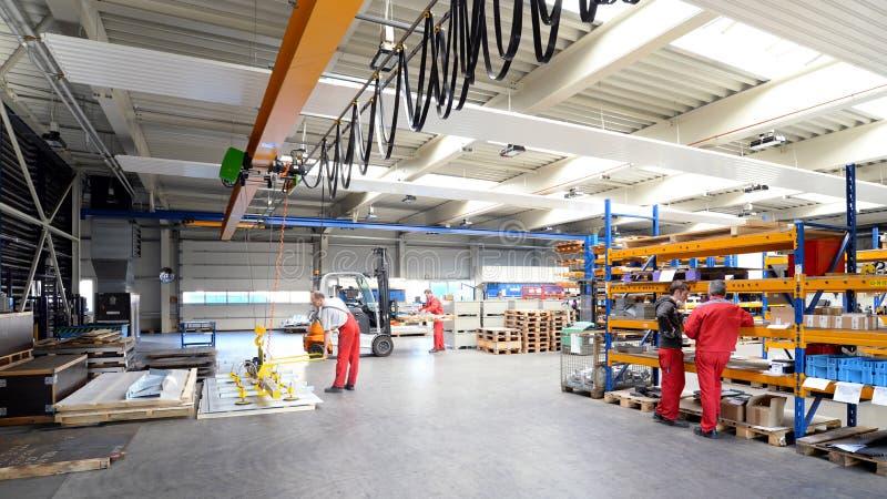 Работники в компании механической обработки - интерьере с машинами в промышленной зале стоковое фото rf