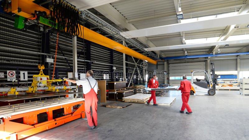Работники в компании механической обработки - интерьере с машинами в промышленной зале стоковая фотография
