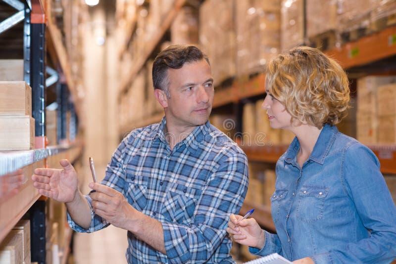 Работники в складе подготавливая товары для отправки стоковые фотографии rf